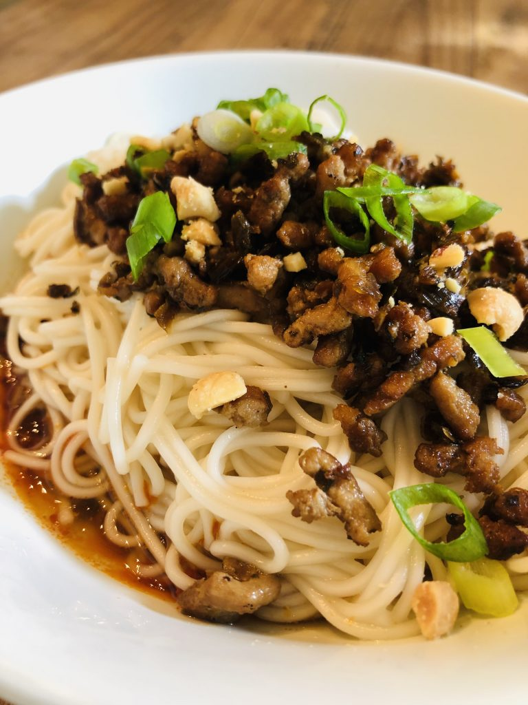Dan dan noodles topped with pork mixture, scallions and peanuts in a white bowl