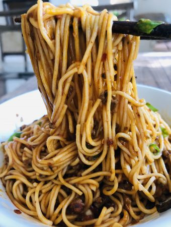 Dan Dan Noodles in a white bowl and some noodles held up by chopsticks