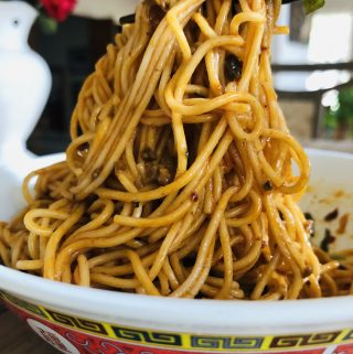 Dan dan noodles in a bowl with chopsticks holding up some of the noodles