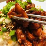 Spicy Chicken Bulgogi With rice garnished with green onions and sesame seeds and chopsticks holding a piece of bulgogi