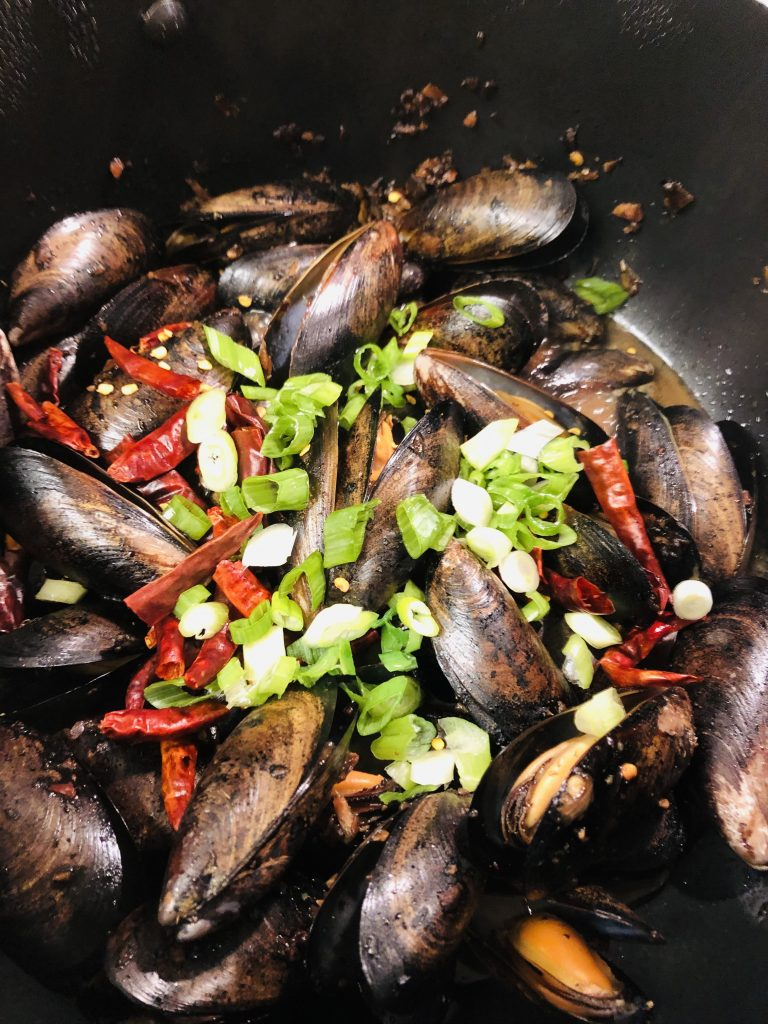 Mussels With Black Bean Sauce topped with dried Asian chilies and chopped green onions
