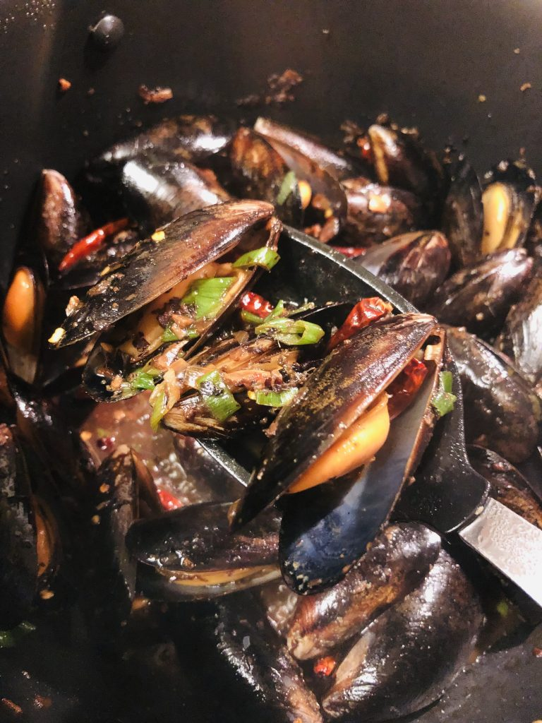 Mussels With Black Bean Sauce garnished with green onions and dried Asian chilies, with a spoon holding some of the mussels